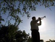 "Jonathan Taylor plays ""Taps,"" the traditional last salute for a military veteran, at his home in Roanoke, Tex. Taylor is a member of Bugles Across America, created a year ago by an Illinois state lottery worker who wanted to connect musicians with families who need them for military funerals."
