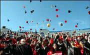 Launching their mortarboards, Lawrence High School graduates, above, and Free State High School, bottom, students signal the end of commencement ceremonies Sunday afternoon in Memorial Stadium at Kansas University.