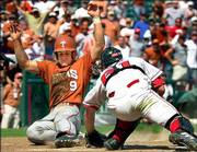 Texas' Ryan Hubele (39) beats the tag by Nebraska catcher John Grose to score the go-ahead run in the 10th inning. The Longhorns won the Big 12 championship, 9-6, Sunday in Arlington, Texas.