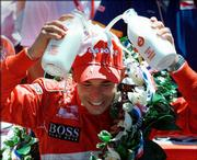 Indianapolis 500 champion Helio Castroneves pours two bottles of milk onto his head. He won his second consecutive Indy 500 on Sunday in Indianapolis.