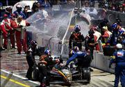 Robby Gordon's car is pushed back toward his pit as crew members and firefighters work to extinguish a fire during the Indianapolis 500. The vent hose from his fuel tank got tangled in the car, igniting a huge fire in the pit Sunday in Indianapolis.
