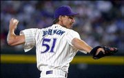 Arizona's Randy Johnson delivers a pitch against Los Angeles. Johnson passed Walter Johnson for eighth place on the career strikeout list Sunday at Phoenix.