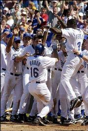 Kansas City's Joe Randa (16) is mobbed by teammates at the plate after hitting a game-winning home run in the bottom of the ninth inning. The Royals won the first game of Sunday's doubleheader, 7-5, and completed the sweep with a 9-8 victory in the nightcap in Kansas City, Mo.