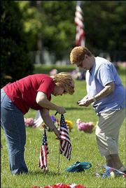 Jackie Wilson, Naples, Italy, left, helps her mother, Emilie Nicholson, Wichita, put flags on the grave of Glenn Nicholson on Monday at Memorial Park Cemetery. Glenn Nicholson, Jackie's father and Emilie's husband, died in the Vietnam War in 1968.