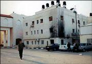 A Palestinian man walks past the compound that serves as Yasser Arafat's headquarters. The building, the site of KU professor Deborah Gerner's meeting with Arafat, shows fire damage on its walls.