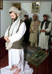 Mullah Mohammed Khaksar, left, former deputy interior minister of the ousted Taliban regime, leads his workers in prayer at his home in Kabul, Afghanistan. Khaksar met with U.S. officials in April 1999 trying to enlist their help in unseating the Taliban.