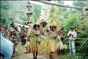 Men and women in traditional dancing dress lead a delegation into a worship service in April in Papua New Guinea.
