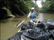 Riverkeeper Dave Murphy of rural douglas County hauls bags of trash down the Kansas River. Murphy and about 25 other volunteers collected more than 40 bags full of trash Saturday from islands and sandbars along the Kansas River during a six-hour float.