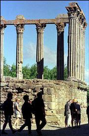 Tourists pass by the Roman Temple of Diana in the heart of Evora's historical center. Romans and Moors are among the ancient peoples who have left their architectural imprint on Portugal.