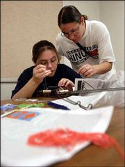 Brandy Juarez, left, Fairview, gets help with her beadwork from instructor Robin Shield during an Upward Bound Summer Academy class.