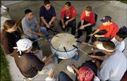 A small group of Upward Bound Summer Academy participants beat a drum and sing American Indian songs at Haskell Indian Nations University. About 55 teen-agers are participating in the academy.