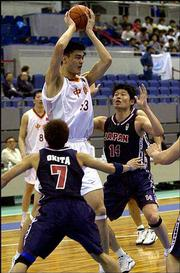 China's Yao Ming (13) holds the ball over Japan's Hidekazu Ishizaka (14) and Makoto Okita (7) during the Third East Asian Games last year in Osaka, western Japan. Yao is expected to be the top pick in Wednesday's NBA draft.
