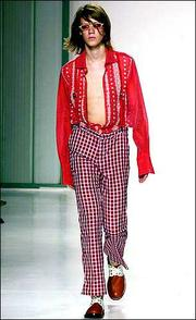 An open shirt is worn with checkered trousers at the Romeo Gigli men's fashion collection.