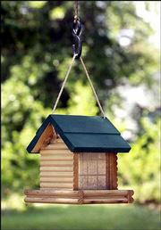 A log cabin-style birdhouse keeps the seed dry and provides a roost.