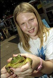 Louise Bouye, 10, Lawrence, shows the frog she entered in the jumping-frog contest during the Lecompton Territorial Day festival. Bouye attended the outdoor event Saturday with her grandmother, Anna Marie Hickock, of Lecompton.