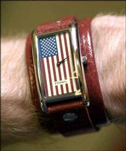 A men's Fossil watch from Weaver's, 901 Mass., features a red leather band and an American flag on the watch face.