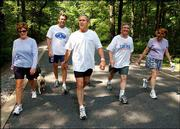 President Bush and first lady Laura Bush, left, complete a four-mile walk with brother Marvin Bush, second from left, Chief of Staff Andy Card, second from right, and Card's wife, Kathleene, after the president underwent a colorectal screening procedure Saturday at Camp David.