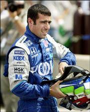 Dario Franchitti stows his earpiece in his helmet after winning the pole during Saturday's qualifying for the CART Grand Prix of Chicago in Cicero, Ill. The Scotsman won the pole with a speed of 158.118 mph.
