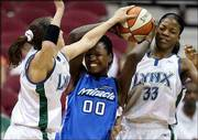 Orlando's Clarisse Machanguana, center, is sandwiched between Minnesota's Svetlana Abrosimova, left, and Janell Burse. The Lynx defeated the Miracle, 67-59, Saturday in Minneapolis.