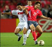 South Korea's Song Chon Gug, right, and Turkey's Yildiray Basturk go after a possession. Turkey won the third-place World Cup match, 3-2, on Saturday in Daegu, South Korea.