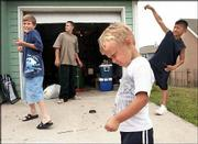 From left, Cole Bagby, 10, Jeremy Johnson, 13, Liam Bagby, 3 and Vienney Phiomavong, 11, toss lit firecrackers and burn sparklers in their Prairie Park neighborhood. Wednesday's fireworks fun for the boys fell on one of the three days in the year, July 2-4, that fireworks are legal in the city. Celebrations will be staged today throughout the city to mark Independence Day.