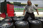 Carlos Fernandes navigates his way through the tires for Scott Sharp's car. Fernandes, a tire specialist for the Kelly Racing team, marked the tires' positions on the car Thursday in preparation for Sunday's Indy Racing League Ameristar Casino Indy 200 in Kansas City, Kan.