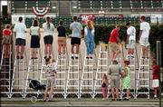 "Baseball fans stand on ladders to peer over the left-field wall outside Joseph P. Riley Park to get a glimpse of the game between the Charleston Riverdogs and the Columbus Redstixx. Monday was ""Nobody Night"" in Charleston, S.C."