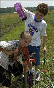 Cooling off during a tour of the Wild Onion Farm southwest of Lawrence, Samuel Faulk, 12, pumps water as Jacob Breithaupt, 13, pours cold water on Samuel's head. The boys visited the farm Tuesday during a weeklong Local Food to Local Kids camp, co-sponsored by Lawrence's Community Mercantile Co-op, the Merc's Education Foundation and the Kansas State Research & Extension-Douglas County.