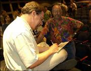 """Michael Feldman of Public Radio International's """"Whad'ya Know?"""" signs an autograph for fan Richard Hopewell of Olathe after the show's taping at the Lied Center. """"Whad'ya Know?,"""" which airs on Kansas Public Radio, was brought to Lawrence to celebrate the 50th anniversary of KPR. KANU 91.5 broadcasts the show at 10 a.m. Saturdays."""