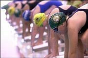 The Lawrence Aquahawks' Emily Smith, right, gets set for her 100-meter freestyle in the 9-10 age group. The final day of the Roger Hill Invitational Swim Meet was Sunday afternoon at the Lawrence Indoor Aquatic Center at Free State High.