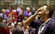 Dan Walsh holds his head as prices fall in the Chicago Mercantile Exchange's Dow Jones futures pit. The Dow dropped 390 points Friday, leaving the index at its lowest point since 1998.