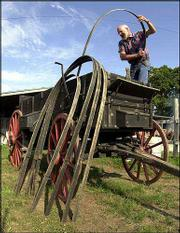 Werner attaches bows to one of the first covered wagons he made outside his shop.