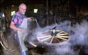 Steam rises as Don Werner sprays water onto a hot iron ring to shrink it onto a wheel at his shop in Horton. Werner has built more than 70 wagons that have been sold in more than 30 states.