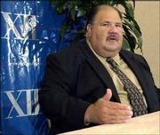 New Kansas football coach Mark Mangino answers a question during the first day of the Big 12 media days in 2002 in Houston.