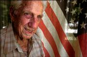 Paul Moore stands outside his house near an old U.S. flag in Salina. The unassuming 86-year-old became part of history as a Navy photographer during World War II when he helped produce one of the more enduring images of the 20th century, the raising of the American flag on the war-torn island of Iwo Jima.