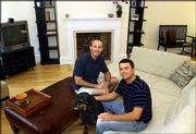 John Repici, left, sits with his partner Adam Slone and their dog Boomer, in the living room of their new home near Logan Circle in Washington. Stock market uncertainty has prompted many investors to look to the real estate market for investments.