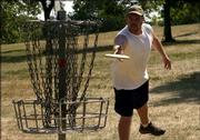 Lawrence's Nathaniel Marshall sinks an easy putt during the Crazy from the Heat disc golf tournament. The Kaw Valley Disc Golf Club held the event Saturday at Centennial Park.