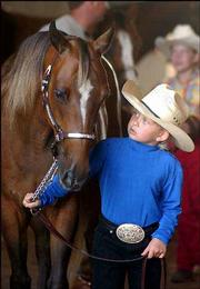 Kailyn Smith, 7, Lawrence, stands with her horse Dime, at the Douglas County 4-H Fairgrounds. Kailyn was showing Dime Saturday in the annual horse show, which kicked off the the week's fair festivities.