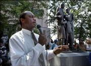 The Rev. Thurmond Tillman leads the crowd in song in Savannah, Ga., during the unveiling of a monument to blacks. The monument the first to blacks in the city where the first slaves to Georgia were delivered has been a topic of debate for 10 years.