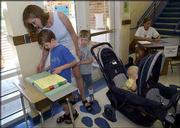 """Adante Ratzlaff, 6, left, and his mother, Jessica, look for Adante&squot;s enrollment information sheet at Pinckney School as they enrolled him for first grade this fall. With Adante on Wednesday were his brothers Brio, 4, center, and Baragan, 11 months, right. A 167 percent increase in enrollment fees has families suffering """"sticker shock,"""" especially for those with more than one student."""