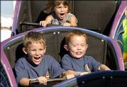 Fair-goers, from left, Alex Cateforis, 5, and Chase Odgers, 4, and in back, Cara Michels, 3, all of Lawrence, ride the Dragon Wagon roller coaster at the Douglas County Free Fair. Fair-goers were greeted Wednesday by a midway that sported spinning and looping rides to test their nerves.