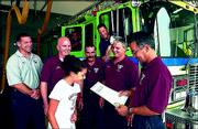 Regional spokesgirl for the Muscular Dystrophy Assn. Jenny McGee, 13, Baldwin, presents a governor's proclamation deeming August Firefighter Appreciation Month to Lt. Joe Mehl, right, and the firefighters at Station No. 3, 3708 W. Sixth St. Also pictured on Monday were, standing, from left, Capt. James Ens, Brian Trigg, Jay Stalcup and Lt. Dennis Leslie, and inside quint truck, from left, Joe Hardy and Scott Nissen.