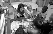Teacher Julie Johnson is surrounded by toddlers at Hilltop Child Development Center. The toddlers learn about shapes and colors.