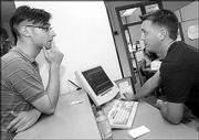 Hutchinson Junior Adam Kruckenberb, left, receives an answer from peer adviser Matt Hughes, Shawnee junior, at the Office of Student Financial Aid.