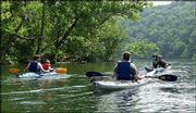 """Kayak tour guide Eric Davis, far right, and his companion, """"D-Go"""" the dog, give instructions to novice kayakers during a trip on Lake Tanneycomo near Branson, Mo. Outdoor adventure companies are drawing a younger crowd to the Ozarks town."""