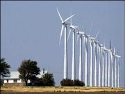 A farm house near Montezuma, about 25 miles southwest of Dodge City, is dwarfed by a row of 13 wind turbines standing 230 feet tall. These electricity-producing, wind-generated turbines are a segment of the 170 machines that are located on 12,000 acres of farmland alongside a stretch of U.S. Highway 56. Farmers are paid about $2000 per year per tower.