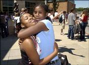 Lawrence High School sophomore Jenesha Jones, left, gets a first-day-of-school hug from her friend and former schoolmate Janae Colter during a sophomore picnic at LHS. Colter, who will be a seventh-grader at South Junior High School, stopped by LHS Wednesday to hug her sophomore friends whom she will no longer have as schoolmates.