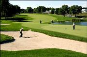 Phillip Prince, left, fires from the sand bunker on to the seventh green as Stephan Ames, right, watches. The two were preparing Wednesday for the PGA Championship, which begins today at Hazeltine National Golf Club in Chaska, Minn.