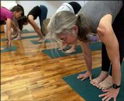 Jill Krebs demonstrates a yoga pose during class at Yoga Center of Lawrence.
