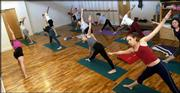 Yoga students emulate poses from instructor Margaret Carr, left, co-director at Yoga Center of Lawrence, 920 Mass.